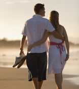 An attractive young couple walking along a beach. Shot is taken from behind